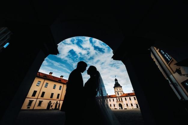 Silhouettes d'un couple amoureux au coucher du soleil sur le fond du château de nesvizh