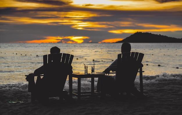 Silhouettes de couple reposant sur des chaises sur la plage