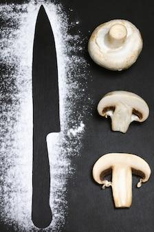 Silhouettes de couteau avec de la farine et du champignon sliesed sur schiste noir