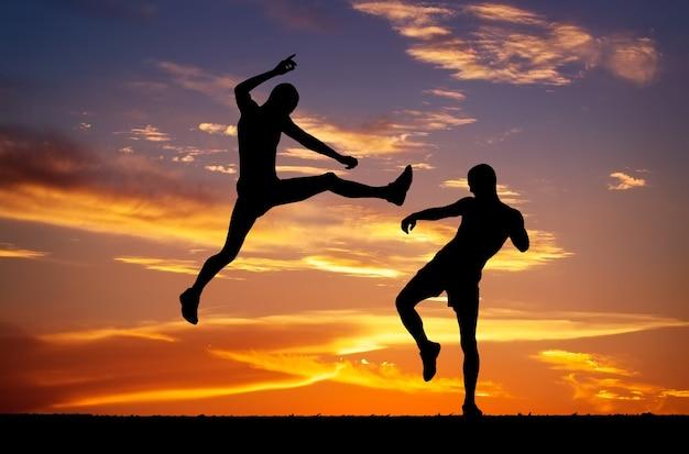 Silhouettes de deux combattants sur fond de feu de coucher de soleil. bataille au coucher du soleil. coup de pied en l'air sur le corps de l'adversaire.