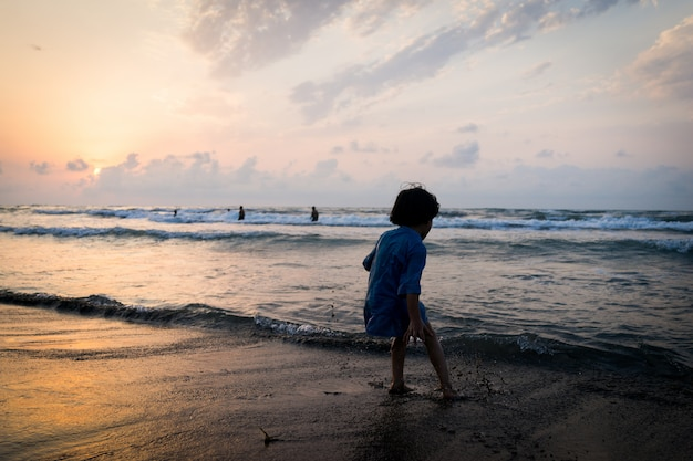 Silhouettes d'enfants ayant un temps heureux sur la plage de la mer près du coucher du soleil