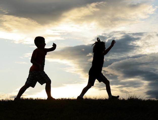 Silhouettes d'enfants heureux s'amuser sur prairie au coucher du soleil célébrant l'été