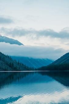 Silhouettes étonnantes de montagnes et de nuages bas se reflétant sur le lac de montagne. belles ondulations sur miroir d'eau. ciel nuageux dans les hautes terres. paysage fantomatique atmosphérique. magnifique paysage de montagne mystique.