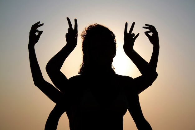 Silhouettes de filles avec les bras levés en plein air