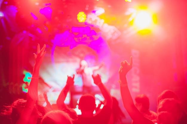 Les silhouettes floues de la foule en concert devant les lumières lumineuses de la scène