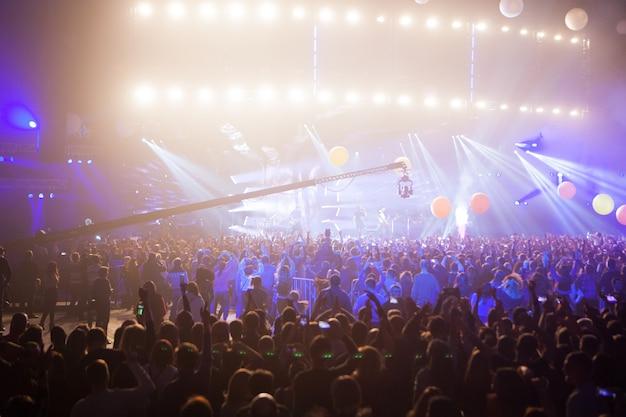 Silhouettes de foule de concert devant les lumières de la scène