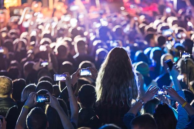 Les silhouettes de la foule en concert devant les lumières vives de la scène. concert d'un groupe de rock abstrait