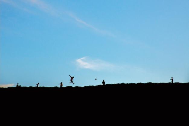 Silhouettes de garçons jouant avec une balle sur la colline sous le ciel bleu