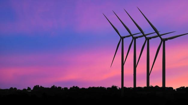 Silhouettes générateurs d'énergie éolienne au coucher du soleil, énergie renouvelable alternative