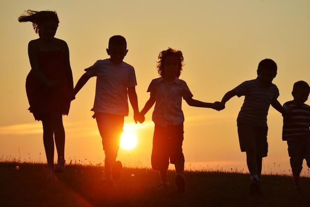 Silhouettes de gens heureux dans la nature au coucher du soleil