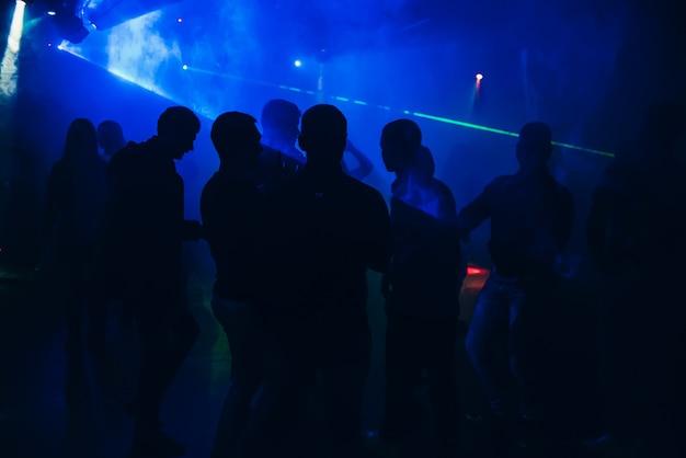 Silhouettes de gens qui dansent dans une discothèque sur la piste de danse à la fête