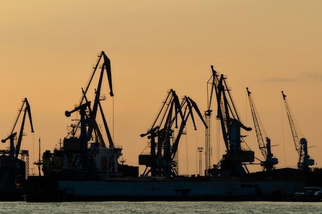 Silhouettes de grues portuaires au fond de ciel coucher de soleil