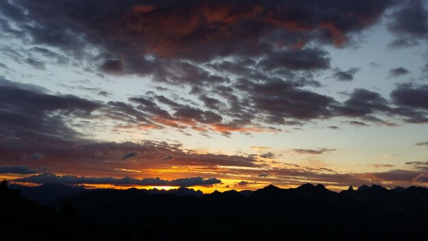 Silhouettes de montagnes rocheuses sous un ciel nuageux pendant le coucher du soleil le soir