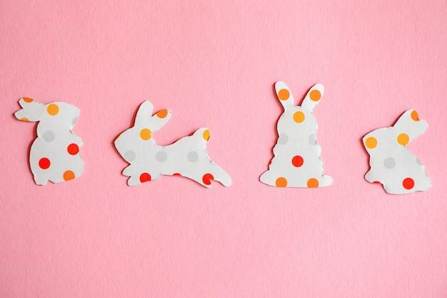 Silhouettes de papier d'un lapin de pâques sur fond rose