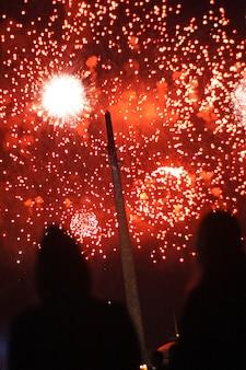 Silhouettes de personnes regardant des explosions de salut rouge colorées dans le ciel. notion de vacances