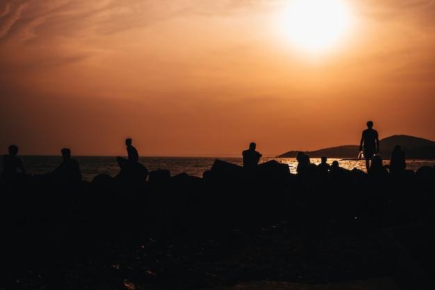 Silhouettes de personnes se reposant sur la plage au bord de la mer contre le coucher de soleil orange