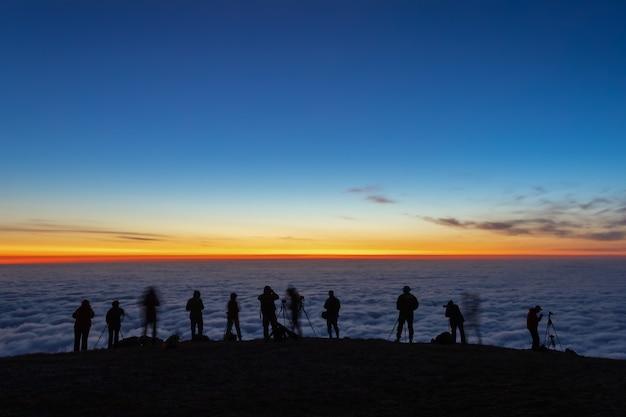 Des silhouettes sombres floues de touristes photographes prennent des photos du lever du soleil du matin