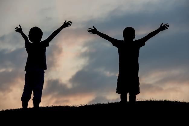 Silhoutte de deux frères jouissant de la liberté