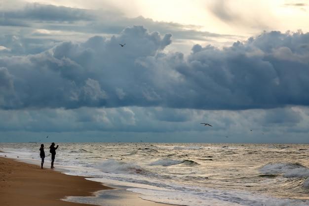 Silhuettes de deux personnes faisant une photo du ciel dramatique sur un paysage marin matinal.