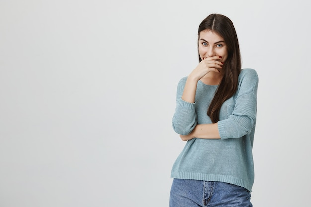 Silly happy woman smiling, couvrir la bouche avec palm