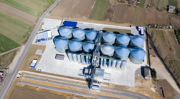 Silos d'argent sur une usine de transformation et de fabrication pour le traitement du séchage, le nettoyage et le stockage des produits agricoles