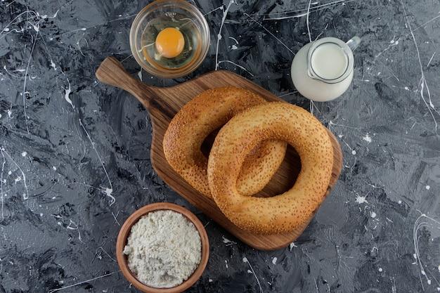 Simit aux graines de sésame et un bol en verre de farine avec œuf de poule non cuit