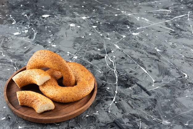 Simit bagel traditionnel turc dans une assiette en bois sur une surface en marbre