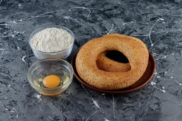 Simit avec des graines de sésame et un bol en verre de farine avec un œuf de poule non cuit.