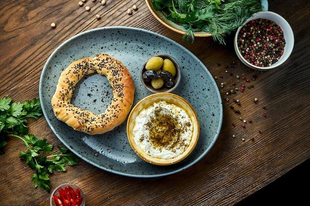 Simit avec mousse de fromage feta à l'huile d'olive et épices, servi sur assiette bleue aux olives. fond de bois. beignet