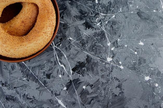 Simit turc traditionnel aux graines de sésame sur une table en marbre.