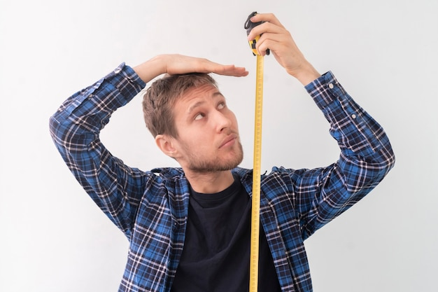 Un simple adolescent adulte de sexe masculin avec un ruban à rouler mesure la hauteur contre le mur