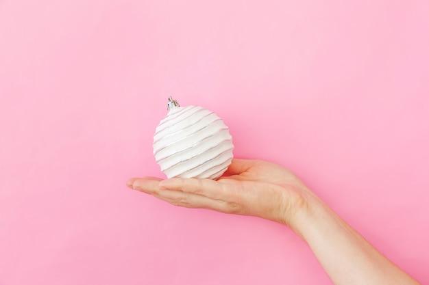 Simplement minimaliste main féminine femme de conception sur boule d'ornement de noël isolé sur fond de tendance coloré pastel rose