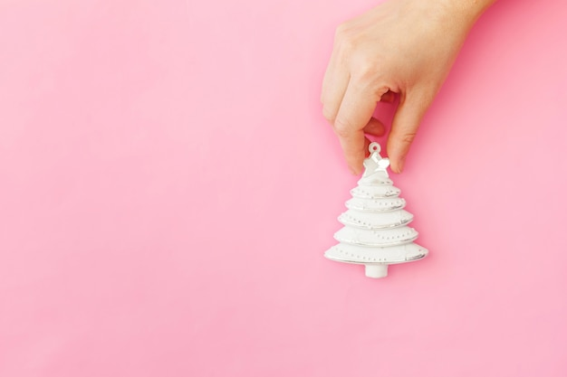 Simplement minimaliste main féminine femme conception tenant noël ornement sapin isolé sur fond de tendance coloré pastel rose