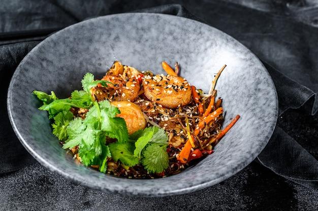 Singapour mei fun. nouilles de riz aux crevettes, crevettes, porc char siu, carotte, oignon, chou napa. fond noir. vue de dessus