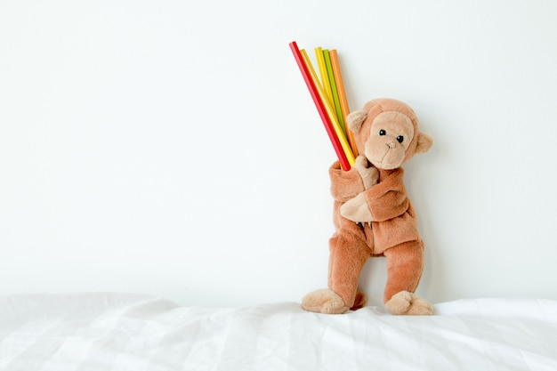 Un singe mignon tient des crayons, il aimerait tout dessiner dans son esprit.