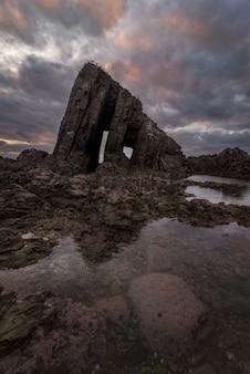 Singulier rocher de la côte au coucher du soleil
