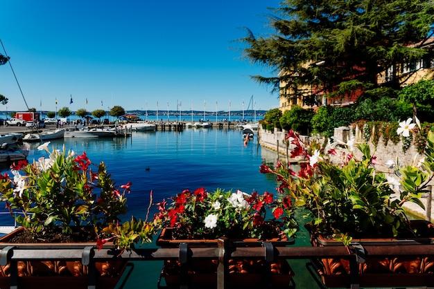 Sirmione, italie - 28 septembre 2021 : bateaux amarrés à côté du château de sirmione sur le lac de garde admiré par les touristes en été.