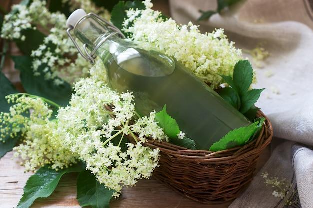 Sirop maison de fleurs de sureau dans un bocal en verre et branches de sureau sur une table en bois de style rustique.