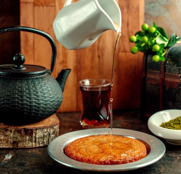 Sirop versé sur le dessert kunefe