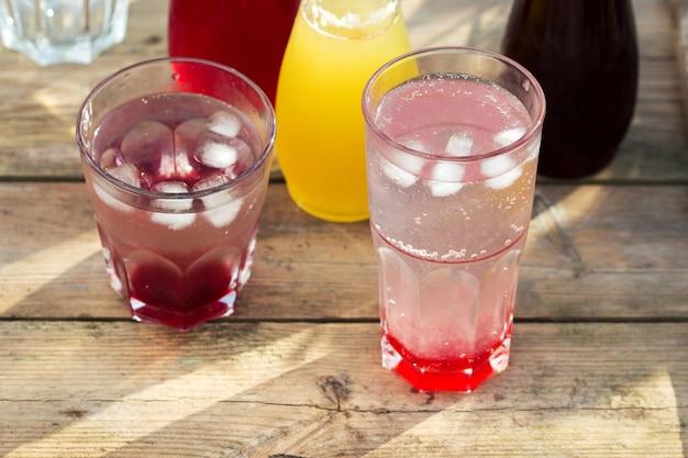 Sirops de fraise, cerise et rhubarbe et verres avec de l'eau sur une table en bois dans le jardin.