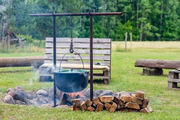 Site de feu de camp avec des bancs en bois près de la maison de campagne.
