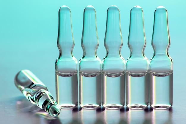 Six ampoules médicales en verre avec un liquide clair sur bleu