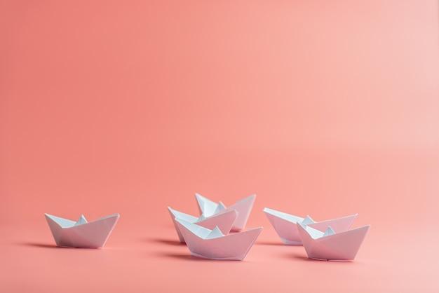 Six bateaux en papier origami sur fond rose.