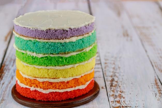Six couches de gâteau de couleur avec de la crème blanche. fermer.