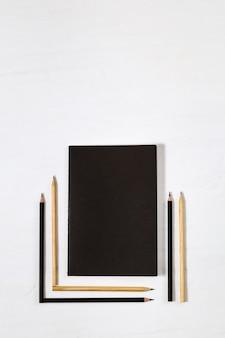 Six crayons en bois et livre noir fermé