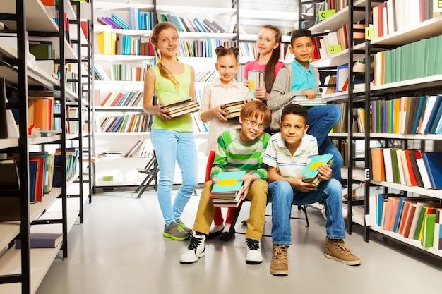 Six élèves ensemble dans la bibliothèque avec des piles de livres