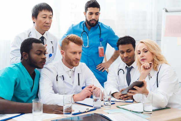 Six médecins de différents pays examinent quelque chose