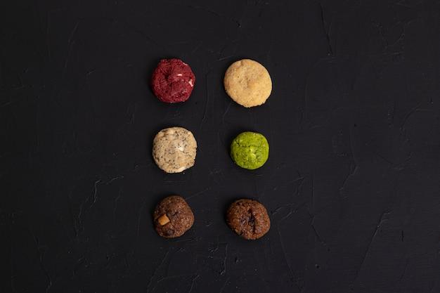 Six mini cookies de différentes saveurs sur fond d'ardoise