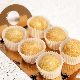 Six muffins traditionnels sous formes papier sur un support en or