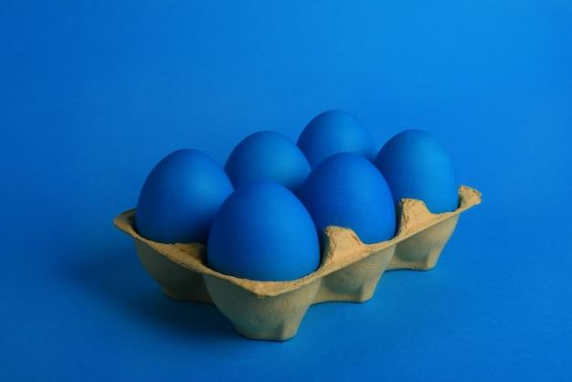 Six oeufs de pâques peints en bleu en emballage jaune sur fond bleu